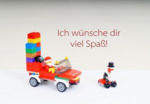 Weihnachtspostkarte. Motiv: ein Weihnachtsmann in einem Weihnachtsmobil aus LEGO. Aufschrift: Ich wünsche dir viel Spaß