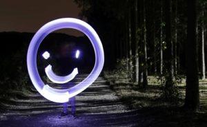 Lightpainting Foto: Ein lila-weißer Smiley, im Hintergrund dunkler Wald