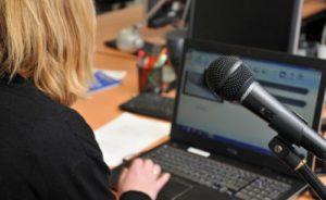 Frau mit Mikrofon vor Audioschnittprogramm