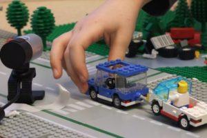 Kinderhand bewegt Lego-Auto vor Kamera