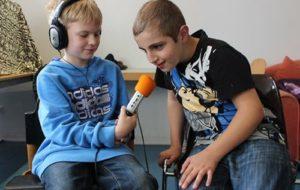 Junge mit Kopfhörer und Mikrofon interviewt anderen Jungen