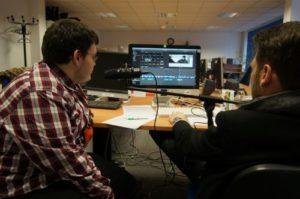 Junge und Mann vor Mikrofon und Laptop mit Audioschnittprogramm