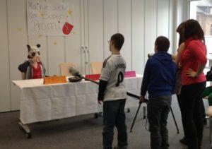 Kinder mit Filmkamera. Am Tisch ein Kind mit Pandamaska. Ein Plakat mit der Aufschrift Mainz sucht den Super-Promi
