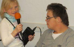 Mädchen mit Mikrofon und Aufnahmegerät und Junge