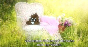 """Filmausschnitt: Eine Blumenwiese mit einem alten Sessel mit geblümten Stoffbezug. Darauf Kacki, der Erzähler - Kothaufen mit Smiley-Gesicht. Untertitel: """"vom letzten Einhorn auf der Suche nach Vielfalt"""""""