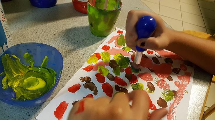Kind gestaltet mit Knaufpinsel eine Karte mit bunten Farbtupfern