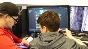 Zwei Jungen vor Laptop, einer tippt auf einem Smartphone
