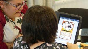 Mädchen vor Tablet, eine Pädagogin unterstützt sie