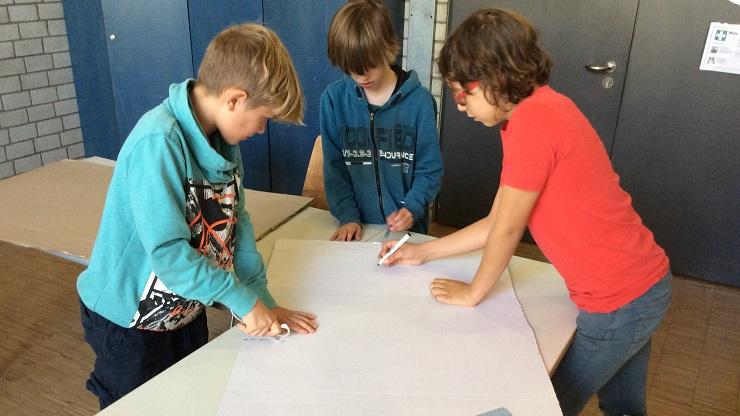 Drei Jungen beugen sich über Flipchartpapier und beginnen zu zeichnen