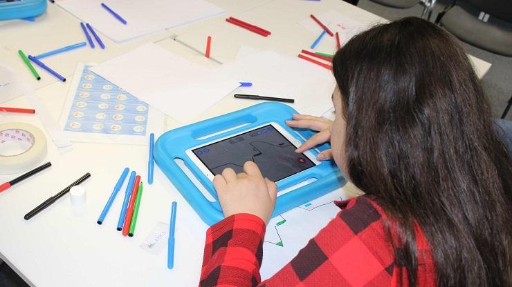 Mädchen vor Tablet in blauer Hülle, um sie herum liegen bunte Stifte verteilt