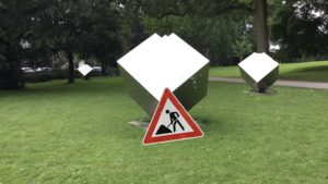Park mit virtuellen Kunstobjekten: Metallene Würfel, Baustellenschild auf dem Rasen
