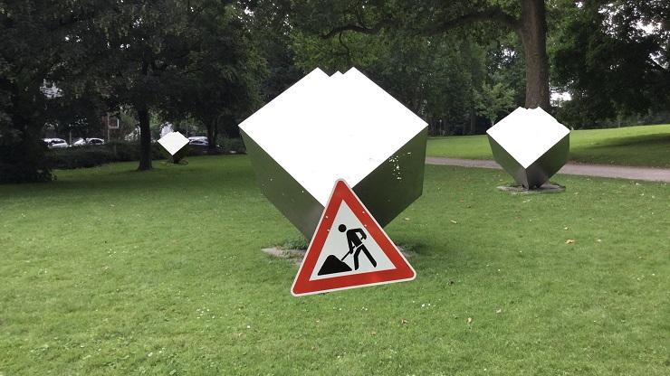 Grünfläche mit virtueller Kunst: Drei abstrakte Stahlwürfel und ein vor dem vorderen Stahlwürfel stehendes Baustellenschild
