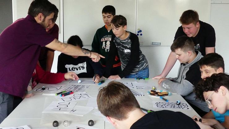 Johannes rück zeigt einer Gruppe Jungen, wie man die Mini-Roboter ozobots über aufgemalte Farbcodes steuert