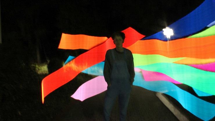 Junge vor Lightpainting-Motiv mit vielen bunten Farben vor dunklem Hintergrund