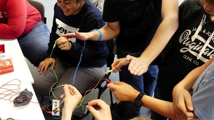 Teilnehmende des inklusiven Jugendcamp halten in der Hand die stromleitenden Klemmen der MaKey MaKey Platine