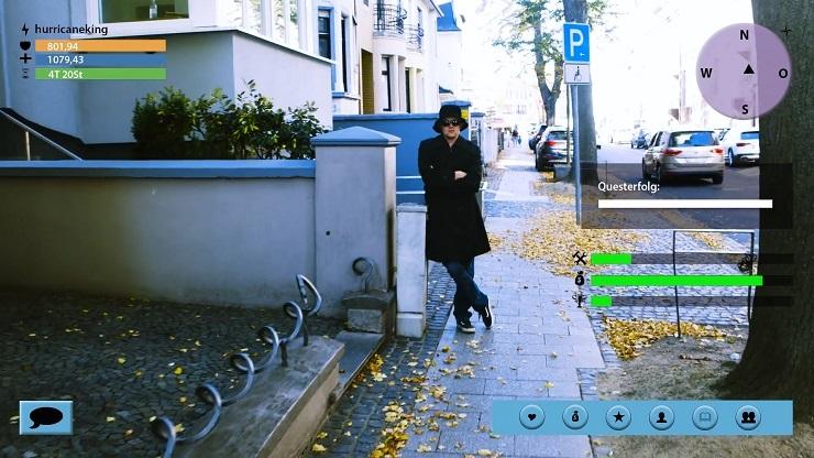Filmausschnitt: Ein junger Mann in schwarzem Mantel, mit schwarzem Hut und mit schwarzer Sonnenbrille steht mit verschränkten Armen an einem Hauseingang. Eingefügte grafische Elemente (z. B. Lebenspunkte, Steuerung) lassen die Szene wie aus einem Computerspiel aussehen