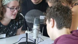 Junge und Mädchen mit zwei Pädagogen vor einem Mikrofon