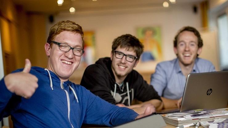 3 junge Männe mit und ohne Lernschwierigkeiten lächelnd vor Laptop, einer zeigt Daumen hoch.