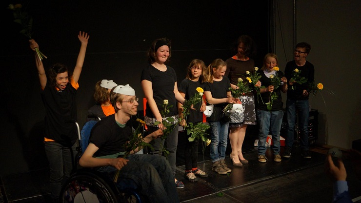 Teilnehmende eines inklusiven Theaterprojekts nehmen beim Schlussapplaus