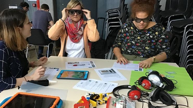 Teilnehmende der Weiterbildung Inklusive Medienarbeit: 2 Frauen testen Apps mit Sehbehinderungsimulationsbrillen