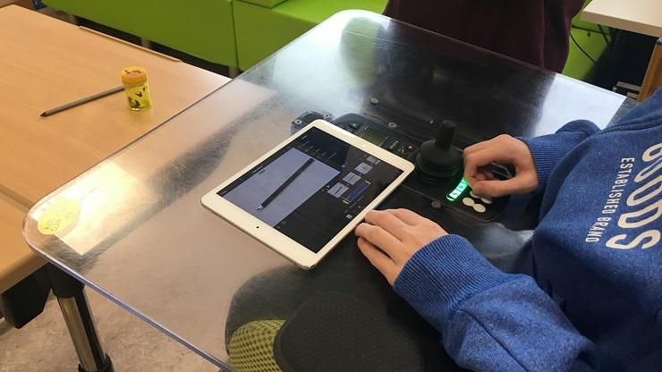 Rollstuhlplatte, befestigt an einem E-Rollstuhl. Darauf ein Tablet, mit dem ein Bleistift fotografiert wird