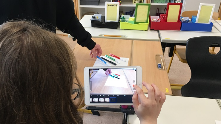 Mädchen filmt farbige Stifte mit iPad