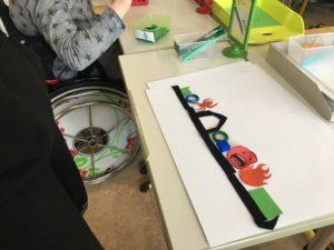 Kind in Rolli. Analoge Gegenstände - z. B. Ringe, farbige Papierausschnitte - werden zu einem Draw-Your-Game-Level auf Papier gelegt.