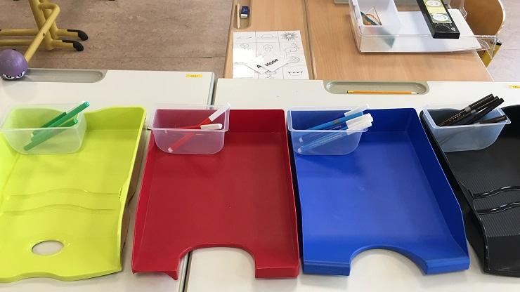 grüne, rote, blaue und schwarze Ablagefächer mit farblich passenden Stiften