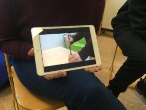 iPad wird auf Schoß gehalten. Gefilmt wird das Anspitzen eines Bleistifts.