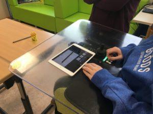 E-Rollstuhl-Platte mit Steuerung. Darauf liegt ein iPad. Gefilmt wird ein Bleistift