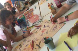 Kinder mit Mal- und Bastelutensilien gestalten Plakate