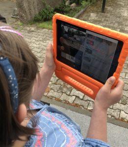 Mädchen filmt mit iPad in orangener Schutzhülle