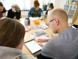 Weiterbildungsteilnehmende arbeiten konzentriert am Tisch mit Laptops