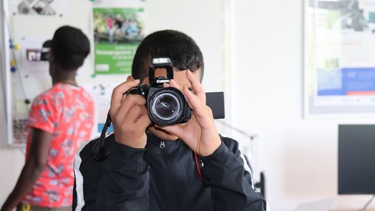Junge mit Kamera vor dem Gesicht