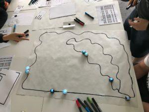 Papierfläche mit aufgemalten Ozobot-Bahnen und Ozobots