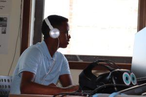 Junge mit Kopfhörer auf am Computerarbeitsplatz