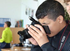 Junge fotografiert mit professioneller Kamera