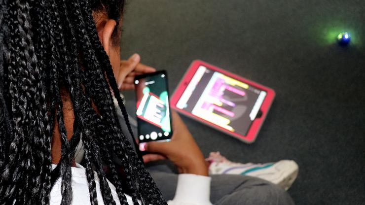 Mädchen filmt mit ihrem Handy ihr selbstentwickeltes Ozoblockly-Programm auf dem Tablet