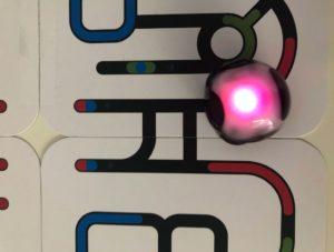 Pink blinkender Ozobot fährt auf Bahn, die aus Karten gelegt wurde