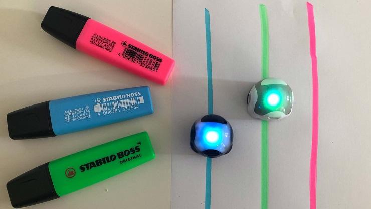 Textmarker in pink, blau, grün. Blaue, grüne, pinke Linie. Zwei Ozobots fahren über die blaue und grüne Linie und blinken blau und grün.