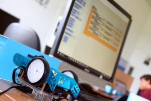 mBot Roboter vor Bildschirm mit Scratch-Programm