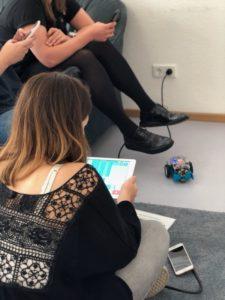 Frau sitzt auf Boden und hält Tablet, links zwei Personen auf Couch, auf Boden ist kleiner Roboter