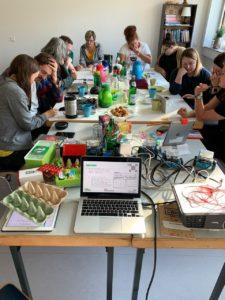 langer Tisch mit Essen, Trinken und Technik, jeweils zwei Personen sitzen zusammen mit Stift und Papier