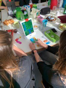 zwei Frauen sitzen an Tisch, vor Ihnen steht hochkant ein Tablet, sie bewegen kleine Blöcke auf dem Tisch