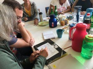 zwei Personen sitzen, eine schreibt mit Stift auf Papier