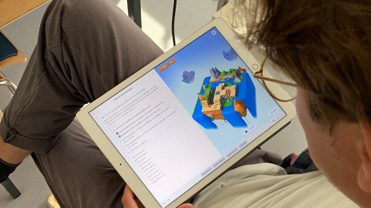 Mann sitzt und schaut auf Tablet mit geöffneter Programmier-App