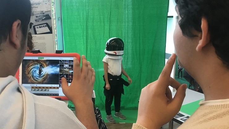 Zwei Jugendliche fotografieren mit der Greenscreen-App ein Kind mit Raumfahrerhelm vor einem grünen Hintergrund