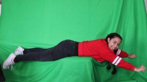 Mädchen liegend vor dem Greenscreen, damit es später aussieht als würde sie fliegen