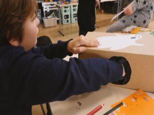 Kind löst ein in Karton verstecktes Fühlrätsel