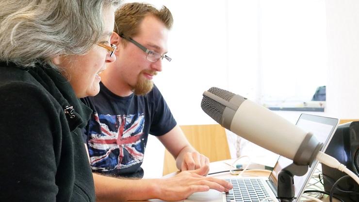 Frau und Mann bei der Arbeit mit Mikro und Schnittprogramm